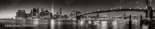obraz PCV Panoramic Black and white view of Lower Manhattan Financial District skyscrapers at twilight with the Brooklyn Bridge and East River. New York City