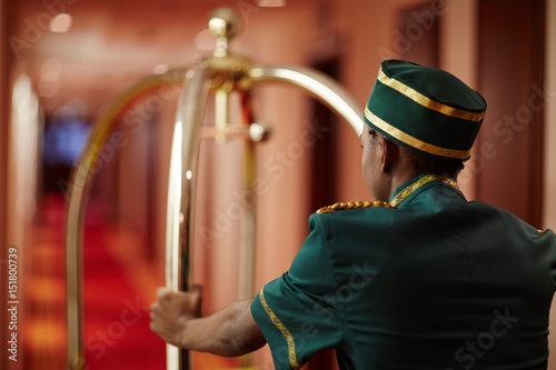 Fotografía  Back view portrait of African-American bellhop pushing luggage cart delivering b
