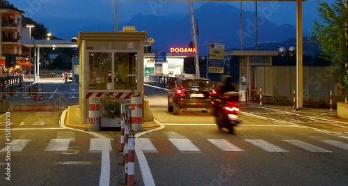 A scooter and a car cross a check point at the Italian-Swiss border