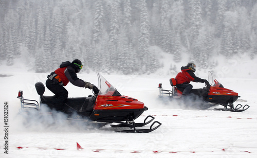 Participants compete in a snowmobile drag-racing competition