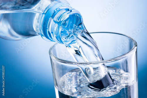 In de dag Water Close-up pouring water from bottle into glass on blue background