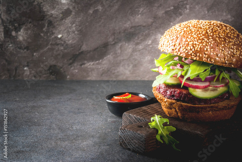 Healthy vegan burgers with beets, carrots, spinach, arugula, cucumber, radish and tomato sauce, whole grain buns on a rustic wooden board on a dark stone background, selective focus, copy space