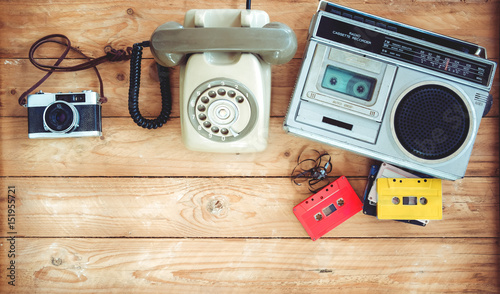 Top view hero header - retro technology of radio cassette recorder with retro tape cassette, vintage telephone and film camera on wood table Canvas Print
