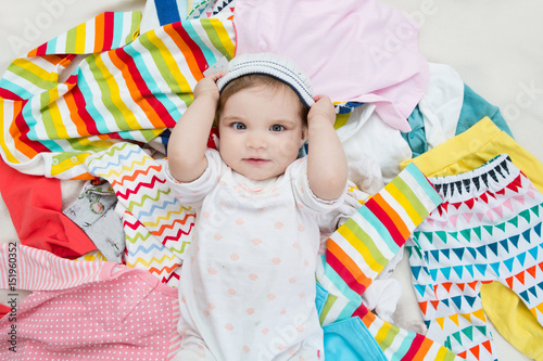 Happy baby girl puts on a cap on background with clothing Canvas Print