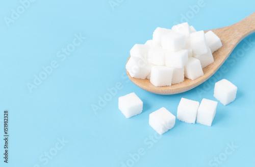 Vászonkép Closeup sugar cubes on wooden spoon white blue background