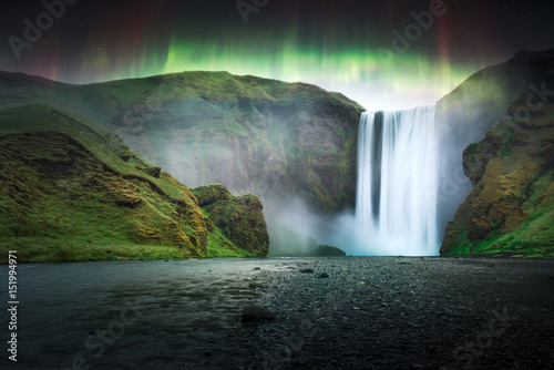Poster Aurore polaire Green aurora light behind famous Skogafoss waterfall