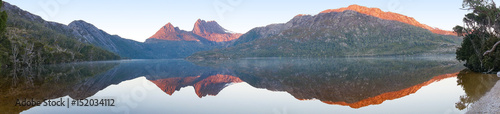 Poster Reflectie Beautiful panorama of mountain range reflected in lake on sunrise