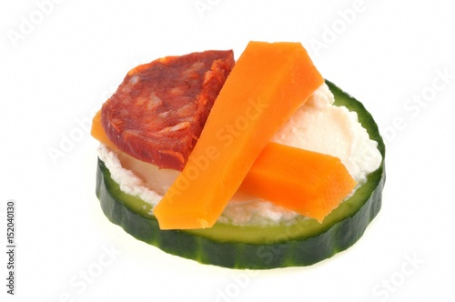 Foto op Plexiglas Voorgerecht Amuse-bouche avec rondelle de concombre, fromage frais, chorizo et mimolette