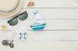Top view accessories to travel beach.vintage sailboat sunglasses hat bicycle with shell on wooden background.