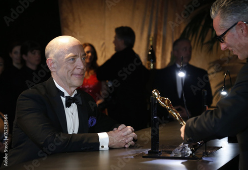 J K  Simmons watches as his best supporting actor Oscar