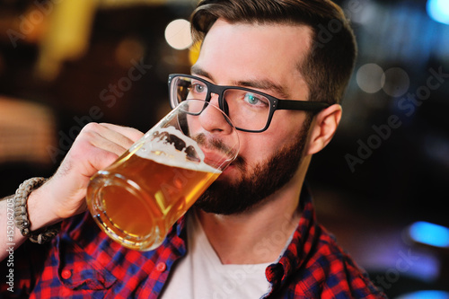 Fotografie, Obraz Bearded handsome man in a plaid shirt with a glass of beer