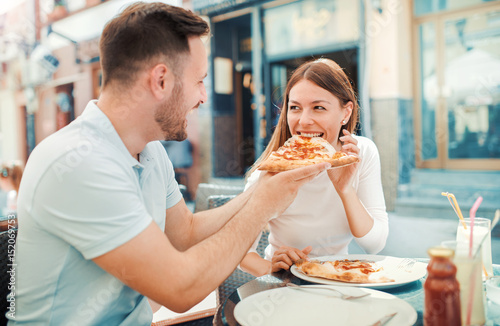 Beautiful young couple sitting in the cafe and eating pizza. Consumerism, food, lifestyle concept