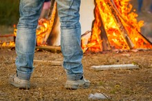 Man In Blue Jeans Looking At The Burning Bonfire Stock Image.