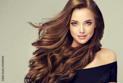 Foto op Plexiglas Kapsalon Brunette girl with long and shiny wavy hair . Beautiful model with curly hairstyle .