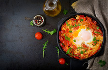 Breakfast. Fried Eggs With Vegetables - Shakshuka In A Frying Pan On A Black Background In The Turkish Style. Flat Lay. Top View