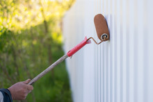A Male Hand Paints A White Metal Outdoor Fence With A Roller