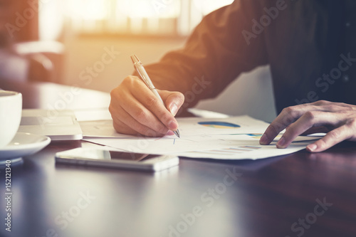 Fotografie, Obraz  Young business man hand writing paper in the office with sunlight