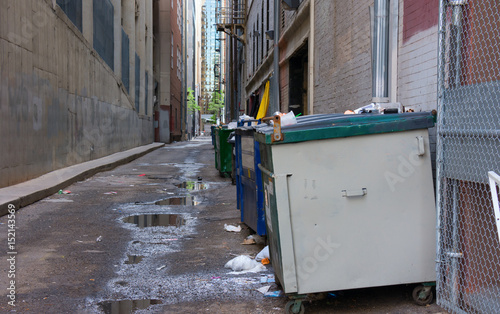 Photo Dirty filthy back alley with dumpsters, old trash, awful puddles filled with a b