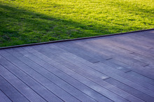 Texture Of Wooden Outdoor Floor With Green Grass On The Background On A Sunny Day.