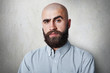 Leinwanddruck Bild - A confident bald male with thick black eyebrows and beard wearing checked shirt having gloomy expression posing against white background.People, fashion, lifestyle concept.