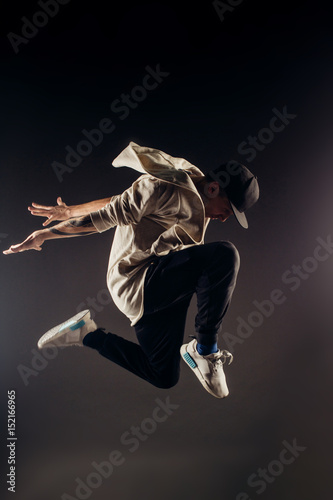 Fototapeta Jumping young male dancer on grey background