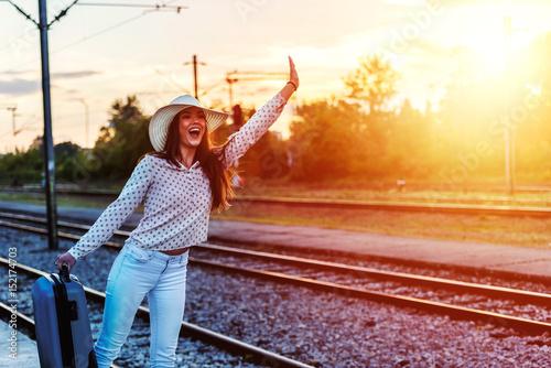 Plakat Młody uśmiechnięty kobieta podróżnik z bagażem blisko torów szynowych machać
