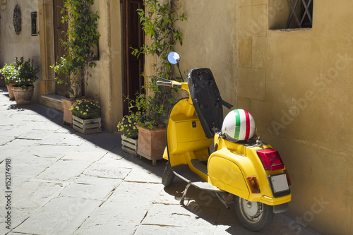Türaufkleber Scooter yellow motorcycle near the wall in tuscany city
