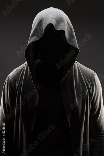 Fotografía  mysterious man in the hood with hidden face over dark grey background