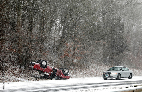 A Connecticut State Police vehicle stands by a flipped over