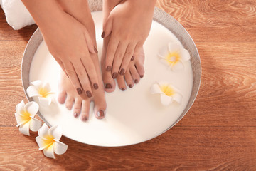 Obraz na płótnie Canvas Female feet and hands with brown manicure in spa bowl with milk