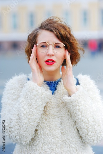 Portrait of a young beautiful perplexed woman walking on square in St. Petersburg spring day on blurred background. Closeup. Wall mural
