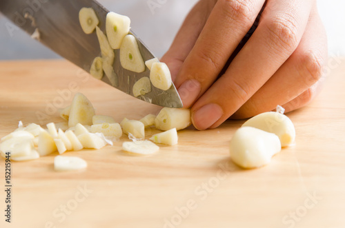 Woman chopping garlic on wooden board for cooking