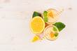 Freshly blended orange citrus smoothie in glass jars with straw, mint leaf, cut orange, top view. White wooden board background, copy space.