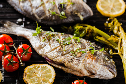 Fotobehang Vis Grilled whole fish, served with roasted vegetables and lemon.