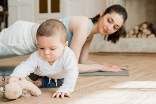 Fotografie, Obraz  Side view of woman doing plank exercise while her son playing with teddy bear