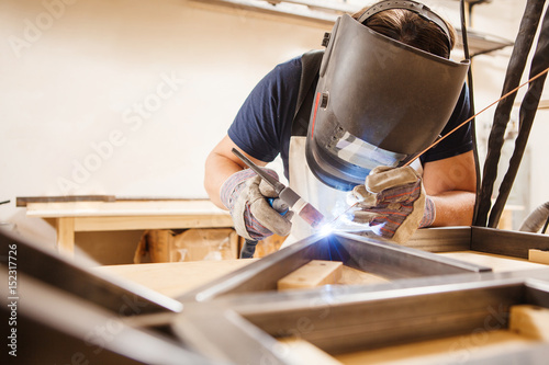 Photo Male in face mask welds with argon-arc welding