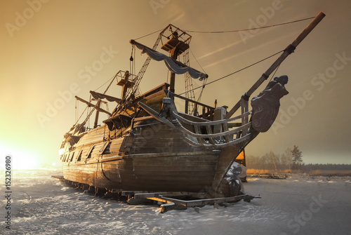 Vintage wooden sailing ship night on the snow in the field