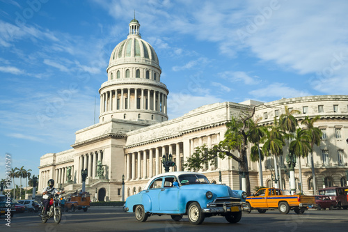 obraz lub plakat Brightly colored classic American cars serving as taxis pass on the main street in front of the Capitolio building in Central Havana, Cuba