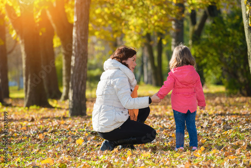 Fotografie, Obraz  Mother talking with a sad child in autumn park