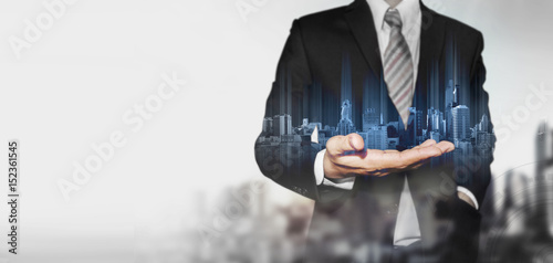 Photo  Panoramic businessman holding blue hologram of modern buildings, with blur backg