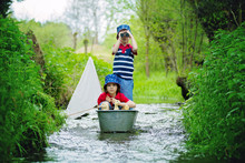 Cute Children, Boys, Playing With Boat And Ducks On A Little Rive