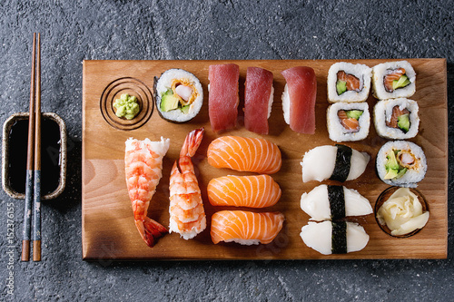 Tuinposter Sushi bar Sushi Set nigiri and sushi rolls on wooden serving board with soy sauce and chopsticks over black stone texture background. Top view with space. Japan menu