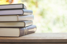 Stack Of Thick Books With Green Light And Bokeh Background