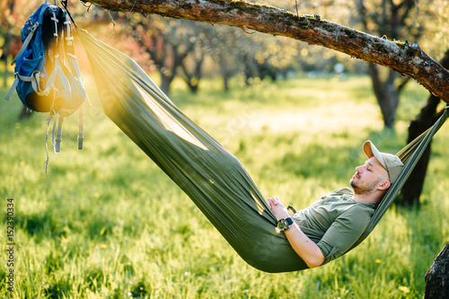 Photo Stands Camping Happy traveler bearded hipster man in green hat and glasses lying in hummock on apple tree in blooming garden in summer sunny day on vacation. Weekend. Tourism. Leisure. Dreaming. Fragrance. Holiday.