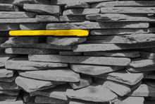 One Yellow Stone In A Wall Of Gray Brick. Gray Stones Are Stacked One On Another.