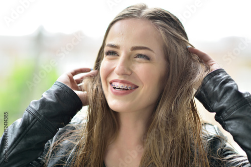 Valokuva  Young attractive woman with bracket system posing rainy spring outdoor and happy smiling