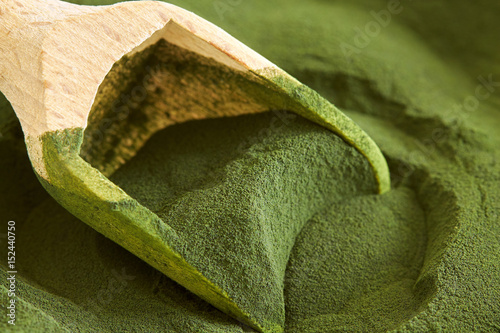 Photo Closeup of chlorella algae powder with wooden scoop