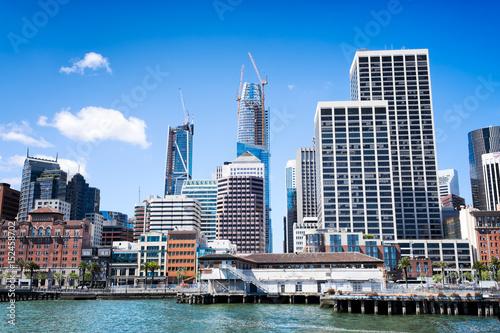 Plakat Nabrzeże San Francisco i panoramę widzianą z zatoki. Ostry obraz budynków starych i nowych, w tym drapaczy chmur w budowie.