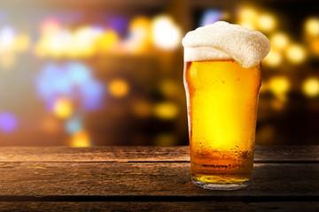 čaša piva na stolu u baru na zamagljenoj bokeh pozadini