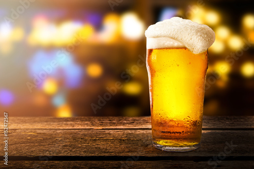 glass of beer on a table in a bar on blurred bokeh background